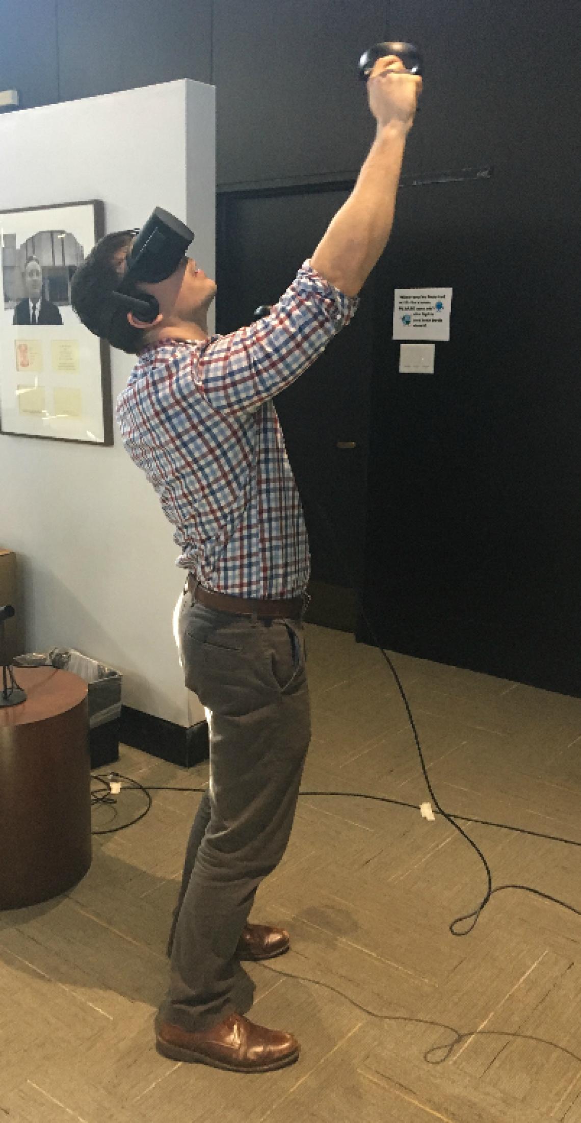 Wearing an Oculus Rift headset and handles to virtually rock climb