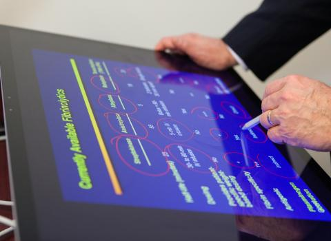 Instructor using tablet to highlight a slide